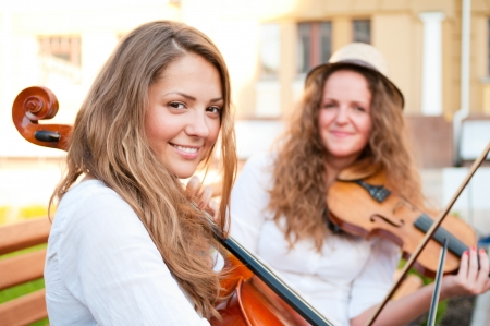 duet: Two women strings duet playing violin and cello on the street of european city