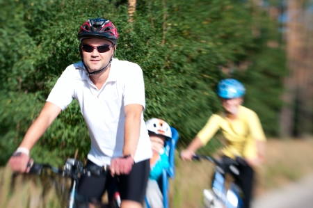 Family on the bikes in the sunny forest with motion blur by lensbaby photo