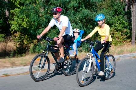holidays vacancy: Family on the bikes in the sunny forest Shot with low shutter speed to achieve motion blur
