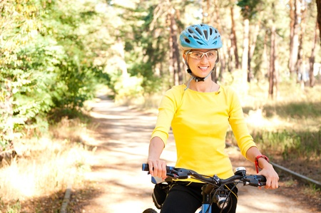 Woman  on the bike in the sunny forest on the pathway photo