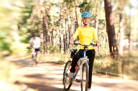 Couple on bikes in the sunny forest with motion blur by lensbaby photo