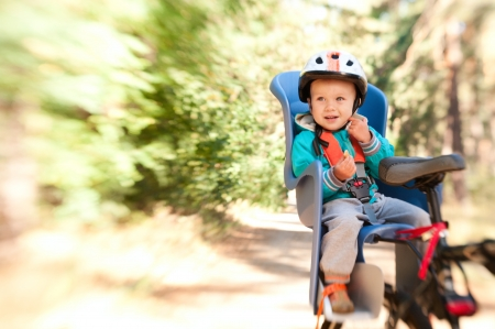 child seat: Little boy in bike child seat outdoors in motion blur by lensbaby Stock Photo