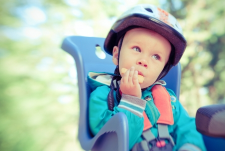 Little boy in bike child seat eating cracker outdoors in motion blur by lensbaby  Cross process