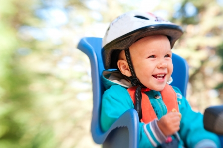 helmet seat: Little boy in bike child seat happy laughing outdoors in motion blur by lensbaby