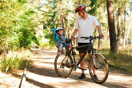 bycicle: Father and little son on bike with child seat in summer forest Stock Photo