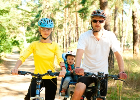 Father, mother and son on the bikes in the sunny forest photo