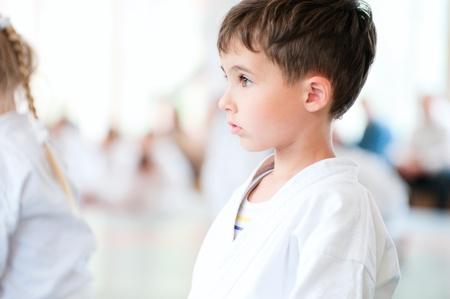 elementary age boy: Karate boy profile portrait with children training in sport hall