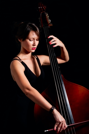 Woman play classic contrabass using bow in low key photo