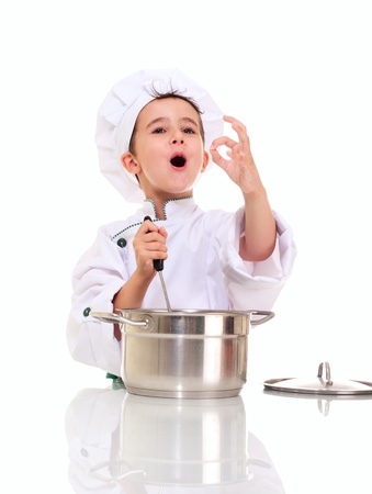 Little singing boy chef in uniform with ladle stiring in the pot ok sign isolated on white