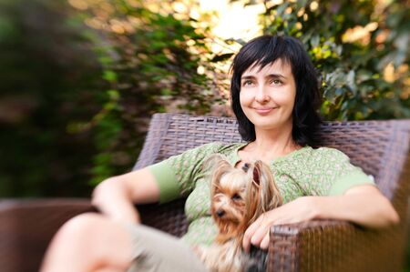 Beautiful woman in chair with little dog in garden relaxing outdoors photo