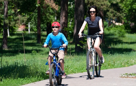 Mother and son riding bikes outdoors in summer park photo