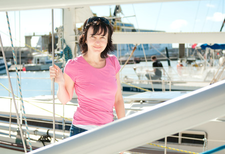 Woman on the yacht in marina in summer photo