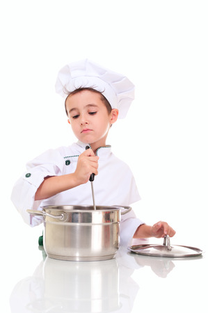 stiring: Little boy chef with ladle stiring in the pot isolated on white Stock Photo