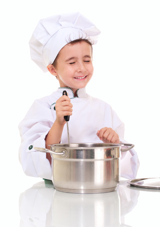 stiring: Little happy boy chef with ladle stiring in the pot isolated on white