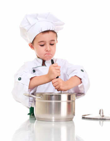 stiring: Little boy chef with ladle stiring in the pot by both hands isolated on white