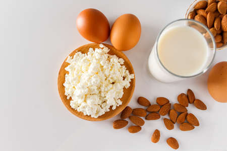 A set of healthy protein foods for a balanced diet. Cottage cheese, eggs and nuts on a white background.