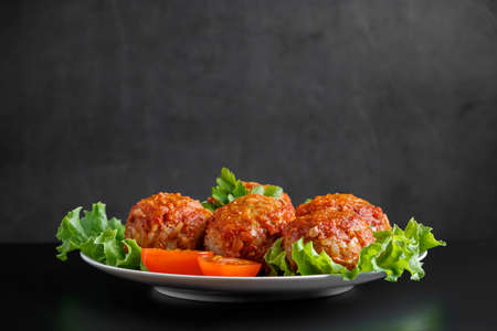 Meat balls in tomato sauce on a black background. Homemade protein meal for healthy eating.