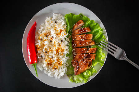 Teriyaki chicken with sesame seeds, lettuce and rice on a white plate. Dish with a fork on a black background