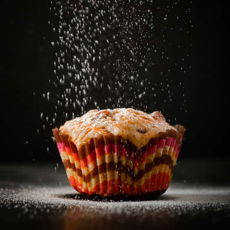 Tasty muffin in icing sugar on a black background. The process of making homemade cake. Standard-Bild
