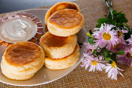 Homemade breakfast - delicious cottage cheese pancakes on a plate with jam and sour cream. Stok Fotoğraf