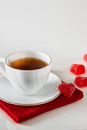 White cup with tea on a red napkin and heart shaped marmalade on a white background. Symbol of love, valentines day, gift card
