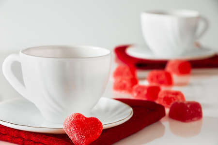 Two white cups of tea on a white background. Heart shaped marmalade, symbol of Valentine's Day and love. The concept of a meeting of two lovers.
