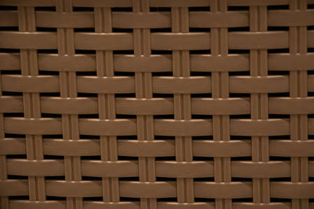 The texture of a yellow plastic wicker basket closeup.
