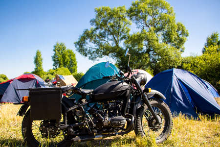 Vintage motorcycle on a sunny summer day at a moto camping. Vintage motorcycle on the background of tents on a sunny day Banque d'images