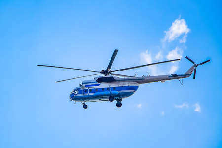 Helicopter flies in the blue sky
