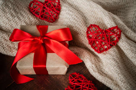 Valentines day surprise in box with red ribbon. Gift for lovers on the background of handmade hearts and a white knitted sweater