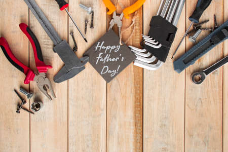 Set of work tools on a wooden background. Festive greeting card concept for Father's day 版權商用圖片