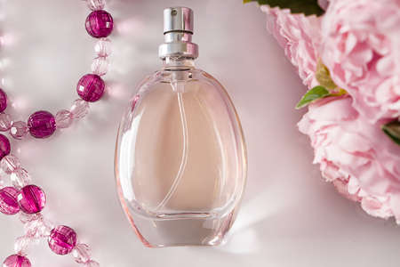 Perfume bottle and flowers on a white background. Fragrant perfume on the background of beads and flowers. Accessories for care on a light background.