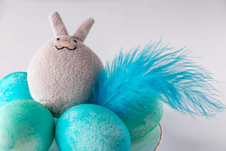 Blue easter eggs and toy rabbit on a white background. Cute toy easter bunny and blue painted eggs with feathers on a white background. Place for your text. Stok Fotoğraf