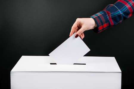 Elections and voting concept. Woman puts ballot paper in a box on a black background. Archivio Fotografico