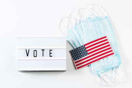 Vote now. Voting concept for the November 3 elections. Medical protective masks and USA flag on a white background.