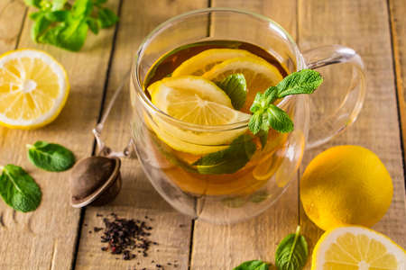 Herbal tea with lemon and mint on a wooden background. Delicious drink for relaxation and alternative therapy of diseases.
