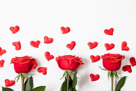 从红色心脏和玫瑰的框架在白色背景。情人节贺卡。布局与文本的地方。