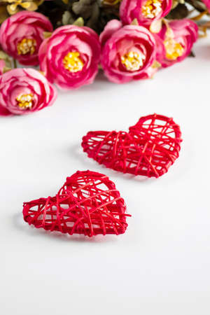 Flowers and red hearts on white background for Valentine's Day.