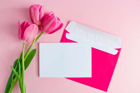Envelope with invitation to holiday and bouquet of tulips on pink background. Place for text.