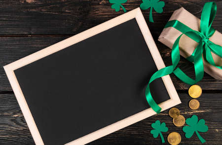 Happy St. Patrick's Day concept. Clover shamrock, gold coins and gift with green ribbon on brown wooden background. Festive composition. Place for text.