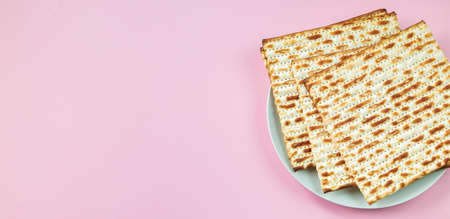 Matzo on pink background. Traditional Jewish food for regilious spring holiday of Pesach. Happy Passover. Copy space, banner format