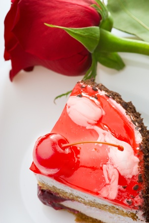 a piece of cake and a red rose Stock Photo