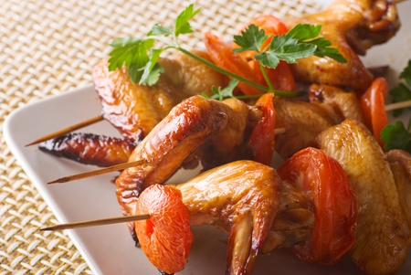 skewers of chicken wings with tomatoes on a plate