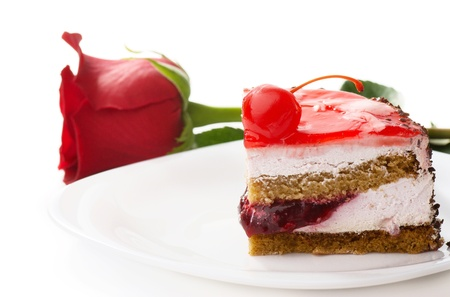 A piece of cake with a red rose lying on a plate