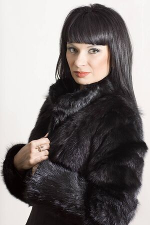 Portrait of a beautiful elegant woman in a black coat on a white background