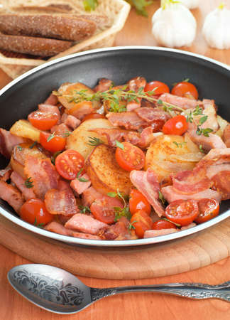 Fried potatoes with meat and vegetables, in a pan Stock Photo