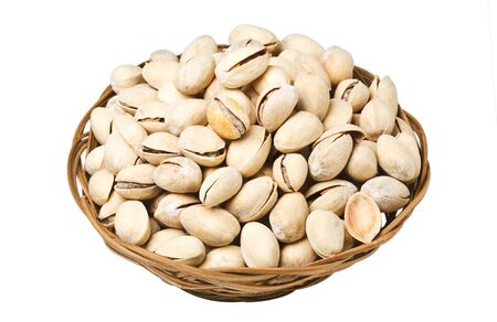 Pistachio nuts in a wicker plate, isolated on a white background