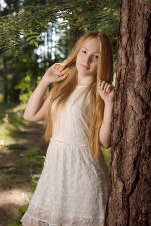 A young girl with long blonde hair standing in the woods near the tree Stock Photo