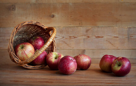 Red apples in a basket on a wooden background Stock Photo