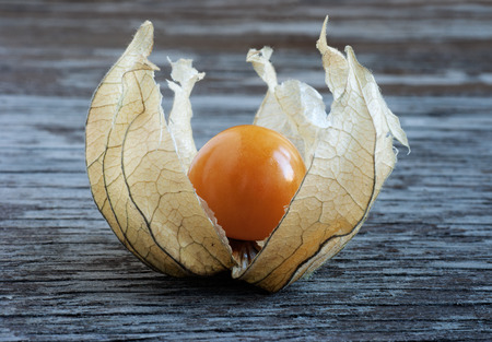 Ripe physalis, lying on a wooden surface Stock Photo